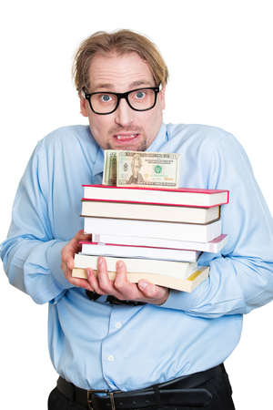 ivy league: Closeup portrait, young worried student man holding books in arms with money, cash on top, looking stressed, isolated white background. Education cost, price of ivy league private school Stock Photo