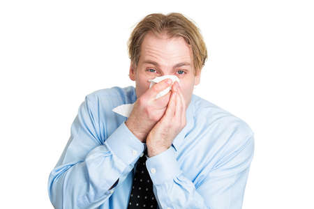 miserable: Closeup portrait sick, ill young business man, student, worker, allergy, germs cold, blowing his nose with kleenex, looking miserable, unwell, very sick isolated white background. Flu season, vaccine Stock Photo