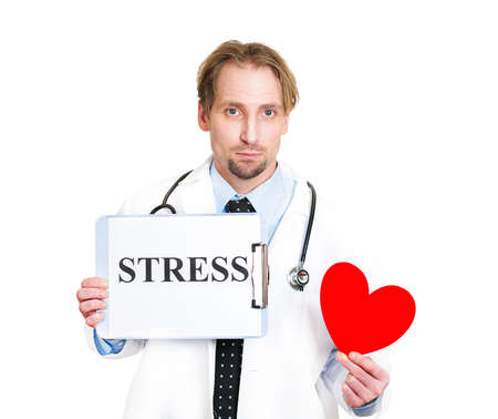 systolic: Closeup portrait serious male health care professional, man family doctor, cardiologist with stethoscope holding sign stress, red heart isolated white background. Patient advise on healthy life style