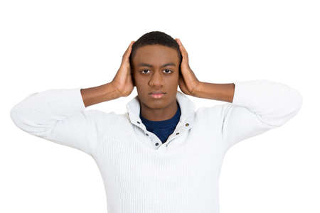repress: Closeup portrait of peaceful, tranquil, looking relaxed, young graduate student man covering his ears, observing, isolated white background. Hear no evil concept. Human emotions, facial expressions Stock Photo