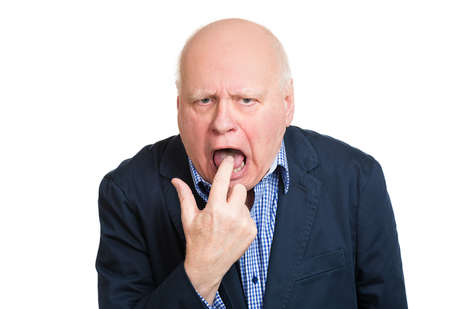 grumpy: Closeup portrait, senior mature unhappy, annoyed, sick business man putting finger in mouth showing something sucks, isolated white background. Negative human emotion, feeling, facial expression, sign