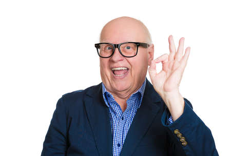 Closeup portrait, happy, cheerful, smiling, senior mature nerd man in black glasses, showing OK sign, isolated white background. Positive human emotions, facial expressions, feelings, attitude photo
