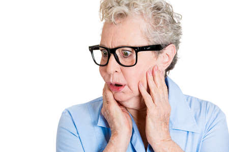 paranoid: Closeup portrait, senior mature woman with big black glasses frames, looking sideways worried, hands on face, paranoid, isolated white background. Positive human emotions, facial expressions feelings