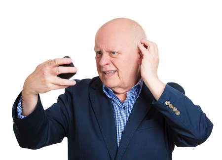 Closeup portrait, senior mature man feeling head, surprised by what he sees on skin or seeing bad news on cellphone, isolated white background. Negative human facial expressions, emotion feeling photo