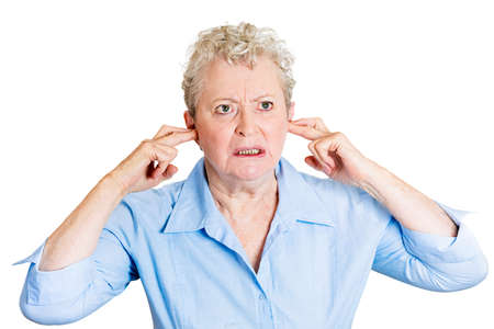 loud noise: Closeup portrait, senior mature angry, unhappy, stressed, woman covering her ears, looking up, to say, stop making that loud noise giving me a headache, isolated white background. Negative emotion