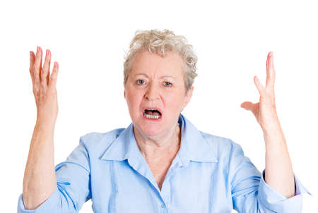 angry boss: Closeup portrait, mad, angry, upset, hostile, senior mature woman, worker, furious employee, yelling, screaming, hands in air, isolated white background. Negative emotions, facial expression reaction