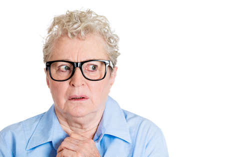 bothered: Closeup portrait, senior mature woman with big black glasses frames, looking sideways worried, hands on face, paranoid, isolated white background. Positive human emotions, facial expressions feelings