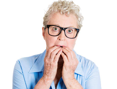 perfectionist: Closeup portrait nervous nerd, senior mature woman in black glasses, bite fingernails craving something, anxious, isolated white background. Negative human emotion, facial expression, feeling reaction