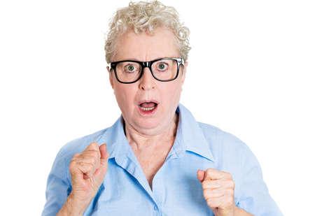 femme bouche ouverte: Portrait de gros plan, senior mature, femme ballot d'affaires dans des verres noirs choqué la recherche, les poings en l'air, isolé sur fond blanc. Émotions humaines négatives, les expressions faciales, les sentiments, les réactions