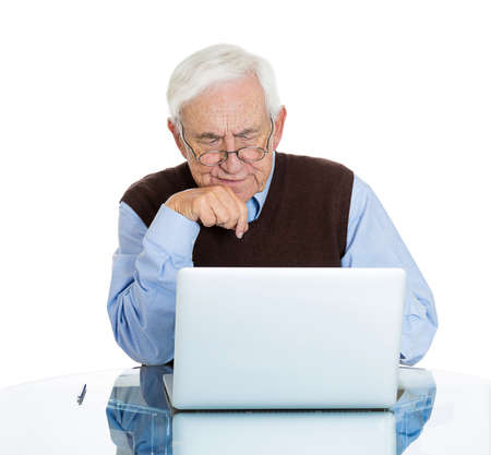 age related: Closeup portrait senior, elderly, mature, man with glasses trying to figure out how use laptop internet isolated white background. Human emotion, facial expression. Age related changes. Old generation