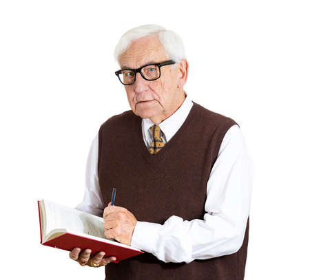 Closeup portrait, senior elderly teacher showing inside book with pen, looking very serious, unhappy, grumpy, isolated white background. Human emotions, facial expressions. Education concept photo