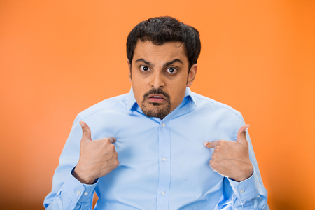 libel: Closeup portrait of angry, unhappy, annoyed young man, getting mad, asking question what is problem, you talking to, mean me? Isolated on orange background. Negative human emotions, facial expressions