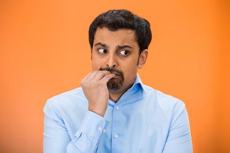 embarrassed: Closeup portrait of young unhappy man, biting his nails looking away with craving for something, anxious, worried isolated on orange, red background. Negative emotions, facial expression, feelings Stock Photo