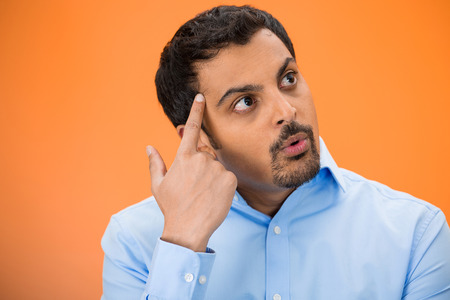 adult oops: Closeup portrait of young man thinking daydreaming trying hard to remember something, finger on head, looking upwards, isolated orange background. Negative human emotion facial expressions feelings.
