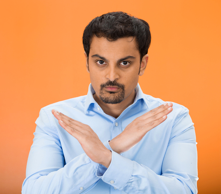 admonish: Closeup portrait of angry young man with X gesture to stop talking, cut it out, dont go there, isolated on orange background. Negative emotion facial expression feelings, signs symbols, body language