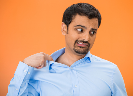 Closeup portrait of young business man opening shirt to vent, its hot, unpleasant, awkward situation, embarrassment. Isolated orange background. Negative human emotions, facial expression, feelings Stock Photo