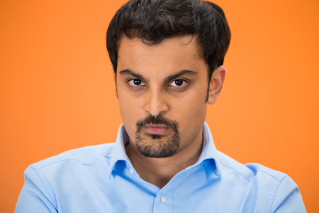 Closeup headshot portrait of displeased, pissed off, angry, grumpy business man with bad attitude, looking at you, isolated on orange background. Negative human emotions, facial expression, feeling