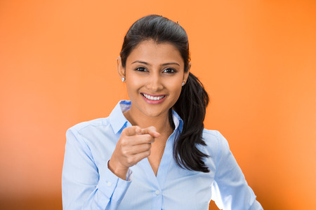 facial expression: Closeup portrait of young, beautiful, excited, happy woman smiling, laughing, pointing finger towards you, camera gesture, isolated on orange red background. Positive human emotion, attitude, reaction