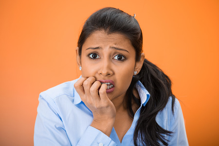 insecure: Closeup portrait of young unhappy woman, biting her nails looking at you with craving for something, anxious, worried isolated on orange, red background. Negative emotions, facial expression, feelings