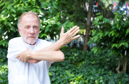 reaching: Closeup portrait, senior mature man in white shirt, stretching arms, isolated green trees background. Warming up Stock Photo