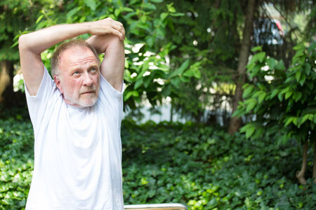 hamstrings: Closeup portrait, senior mature man in white shirt, stretching arms, isolated green trees background. Warming up Stock Photo