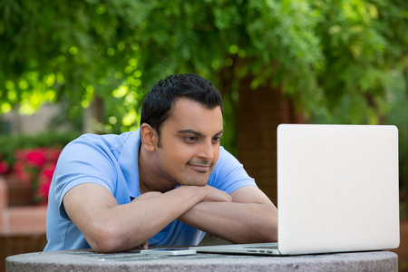 Closeup portrait, young handsome man in blue shirt resting chin on hands, browsing digital computer laptop, isolated background of sunny outdoor, green trees, flowers, nature photo