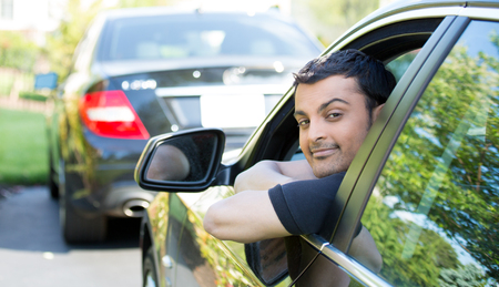 rental: Closeup portrait, young handsome man in his new black car, relaxing, resting face on arms, isolated on outdoors background with vehicle.