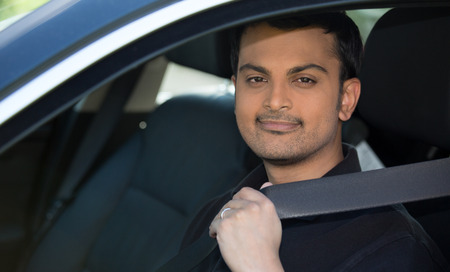 Closeup portrait of young, handsome man pulling on seatbelt inside of black car. Driving safety, buckle up to prevent traffic death and accidents