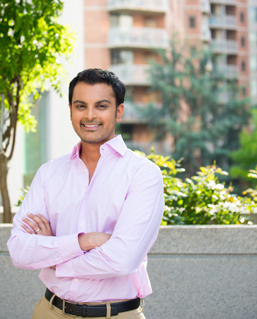 Closeup portrait, happy handsome businessman in pink shirt, arms folded, crossed, relaxing outside of his office during sunny day, isolated city urban balcony background. Corporate success