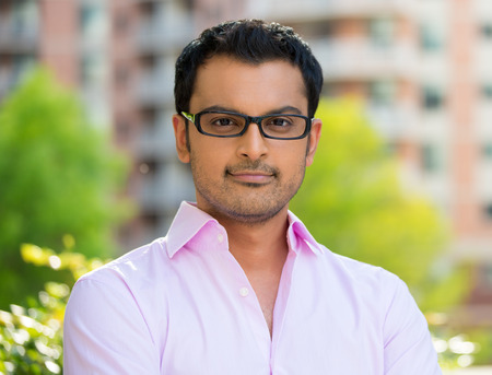 ethnic people: Closeup headshot portrait, happy handsome businessman in pink shirt, wearing black glasses relaxing outside of his office during sunny day, isolated on a city urban background. Corporate success