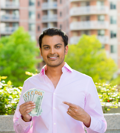 Closeup portrait, super happy excited successful young business man pointing to money dollar bills in hand, isolated background of trees, building. Financial reward photo