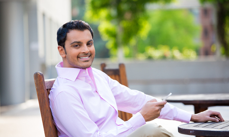 Closeup portrait, young happy businessman sitting, checking his cellphone, isolated on background of a city building, trees, on a sunny autumn day. Corporate life success. Business communication photo