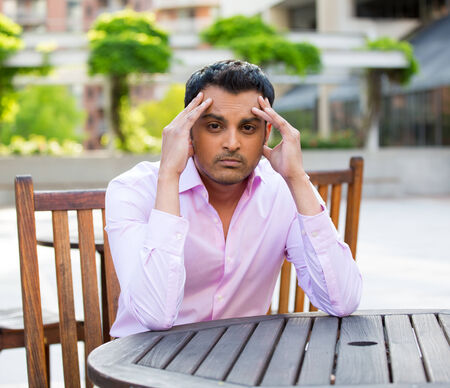 Closeup portrait, stressed young businessman, sitting at table, hands on head with bad headache, isolated background of trees, buildings, outside. Negative human emotion facial expression feelings. Banco de Imagens