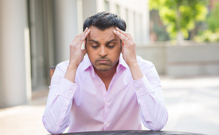 Closeup portrait, stressed young businessman, hands on head with bad headache, isolated background of trees, buildings, outside. Negative human emotion facial expression feelings. Standard-Bild