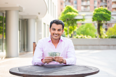 indian currency: Closeup portrait, super happy excited successful young business man holding money dollar bills in hand, isolated background of trees, building. Financial reward Stock Photo