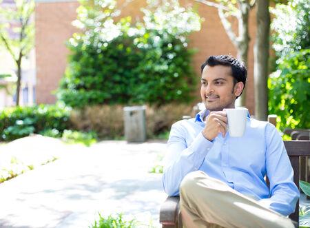 cafe colombiano: Primer retrato, empresa joven taza de consumición fuera del hombre, sentado en el banco de relax, árboles aislados, la creación de fondo