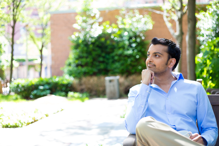reflect: Closeup portrait, smiling, joyful, happy young business man, sitting, daydreaming nice things, isolated sunny outdoors, trees background. Positive human emotions facial expressions feelings