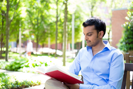 Closeup portrait young business man reading red book, relaxing on wooden bench, sitting outside on sunny day, isolated green trees background