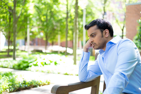 Closeup portrait, stressed young business man, resting face on fist, isolated background of trees outside. Negative human emotion facial expression feelings. photo