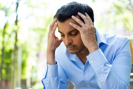 upset man: Closeup portrait, stressed young business man, hands on head with bad headache, isolated background of trees outside. Negative human emotion facial expression feelings.