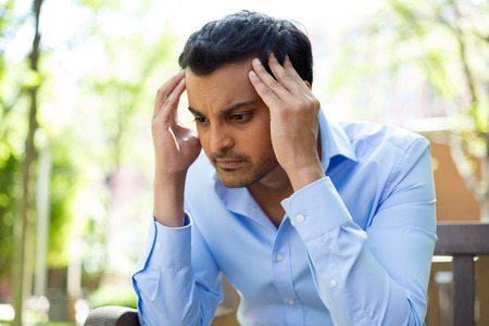 tense: Closeup portrait, stressed young business man, hands on head with bad headache, isolated of trees outside. Negative human emotion facial expression feelings.