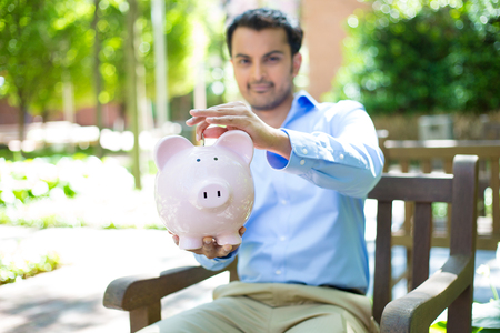 manage: Closeup portrait, young business man putting coins in piggy bank, isolated outdoors trees background. Smart wise currency financial investment wealth decisions. Budget management and savings Stock Photo