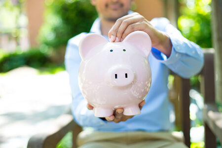 Closeup portrait, young business man putting coins in piggy bank, isolated outdoors trees background. Smart wise currency financial investment wealth decisions. Budget management and savings photo