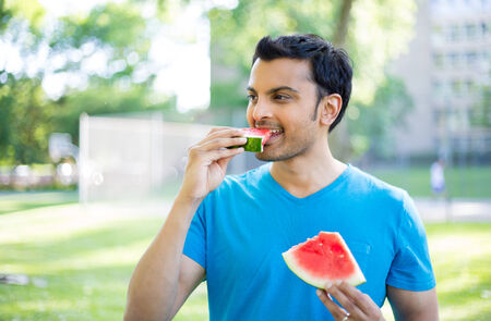 colombian food: Closeup portrait, guy in blue shirt chowing down on watermelon wedge outside, isolated outdoors, green park background. Organic fresh fruit diet Stock Photo