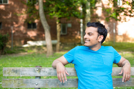 indian boy: Closeup portrait, happy smiling, regular young man in blue shirt sitting on wooden bench, relaxed looking to side, isolate background trees, woods Stock Photo