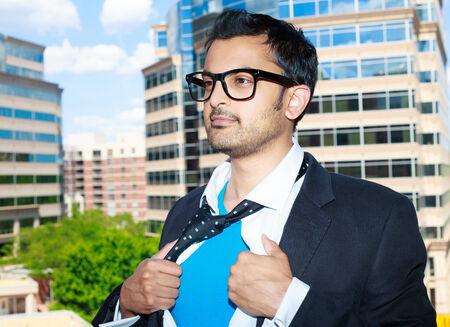 traje mexicano: Primer retrato, joven hombre de negocios con gafas negras de apertura camisa blanca para mostrar traje de superhéroe azul dentro, listo para luchar contra el crimen, edificios aislados de la ciudad árboles de fondo