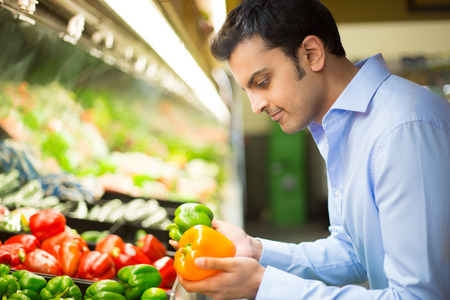 Closeup portrait, handsome young man in blue shirt picking up bell peppers, choosing yellow and orange vegetables in grocery store