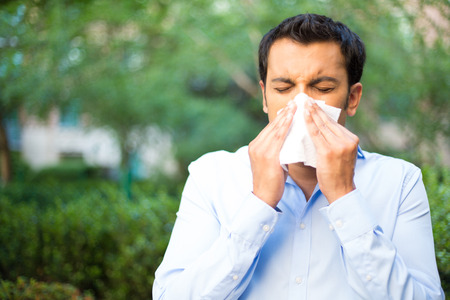 neus: Close-up portret van een jonge man in blauw shirt met een allergie of koude, blazen zijn neus met een papieren zakdoekje, op zoek ongelukkig onwel erg ziek, geïsoleerde buiten groene bomen achtergrond. Griepseizoen, vaccinatie.