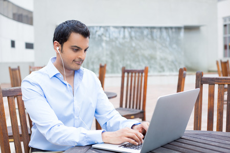 Closeup portrait, young handsome man in blue shirt typing away, listening to headphones, browsing digital computer laptop, isolated background of sunny outdoor, brown chairs background photo