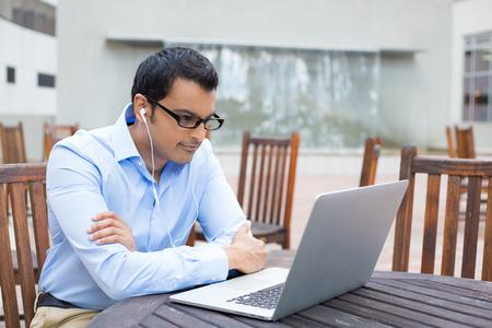 Primer retrato, joven de camisa azul y negro gafas, escuchando a los auriculares, la navegación portátil ordenador digital, fondo aislado del sol, edificio gris al aire libre con sillas de color marrón de fondo Foto de archivo - 31270468